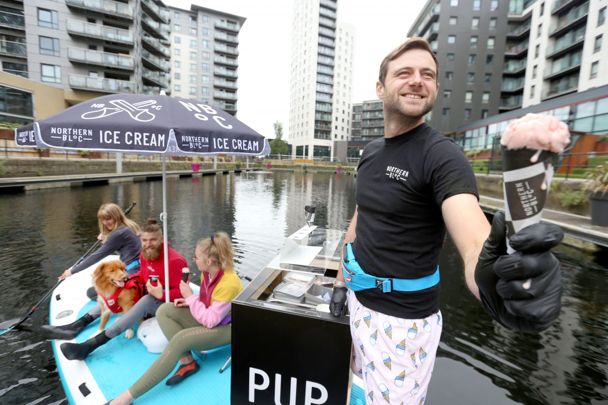 Picture : Lorne Campbell / GuzelianPaddleboard enthusiasts  get an ice-cream from Josh Lee, co-founder of urban ice cream brand, Northern Bloc at the launch of the world's first paddle board ice-cream parlour, in Leeds, on Wednesday morning. Celebrating the start of National Ice Cream Month (1 July) the brand has teamed up with Red Paddle Co to seek the most carbon-friendly way to share its vegan ice creams whilst the sun shines. Trialling the PUP (Paddle Up Parlour) on its home surf, Northern Bloc is trialling its parlour ahead of its next outing at Dogmasters, 2021, the UK dog surfing and SUP championships PICTURE TAKEN ON WEDNESDAY 30 JUNE 2021.FULL PRESS RELEASE BELOWIce Cream Float: worldÕs first paddleboard ice cream parlour makes maiden voyage for start of National Ice Cream Month Vegan ice cream brand trials sustainable summer vehicle on Leeds canal ahead of summer celebrationsPaddleboard enthusiasts from Leeds, Jamie Crowther and Zoe Dawson, proved theyÕve got paddleboarding licked when they took to the water today to try out the worldÕs first paddleboard ice cream parlour, created by urban ice cream brand, Northern Bloc.Celebrating the start of National Ice Cream Month (1 July) the brand has teamed up with Red Paddle Co to seek the most carbon-friendly way to share its vegan ice creams whilst the sun shines.Trialling the PUP (Paddle Up Parlour) on its home surf, Northern Bloc is planning a schedule of pop-up paddleboard ice cream parlours as the UK basks in a staycation summer and the popularity of paddleboarding hits new heights.The customised 17ft long XL Ride inflatable paddleboard ice cream parlour will take to the high seas in Bournemouth this month (25 July) for the UKÕs only Dog SUP Surfing Championships on Branksome Dene Chine beach. The internationally recognised event brings together lovers of dogs and the sea for a fun-packed day of surfing and paddleboarding competitions, as well as live music, food and drink.Red Paddle CoÕs customised  XL Ride